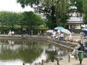 溜め池に糸を垂らす釣り人たち